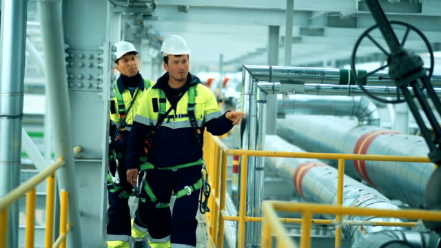 Engineers, in production plant as team discussing, industrial scene in background Engineers, in production plant as team discussing, industrial scene in background. oil industry stock videos & royalty-free footage