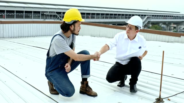 Engineers in rooftop discuss about blueprint.
