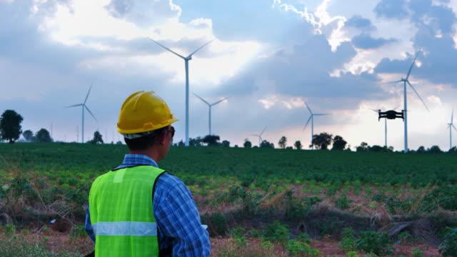 エンジニア男性は、電力の生産のための検査ドローンと風力ファームフィールドに風力タービンの動作をチェックしています。 - コントロール点の映像素材/bロール