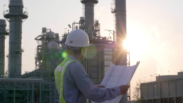 engineers male are looking at blueprint for workers security control at power plant. energy power station area with sky, sunset. concept safety,industry - sottostazione elettrica video stock e b–roll