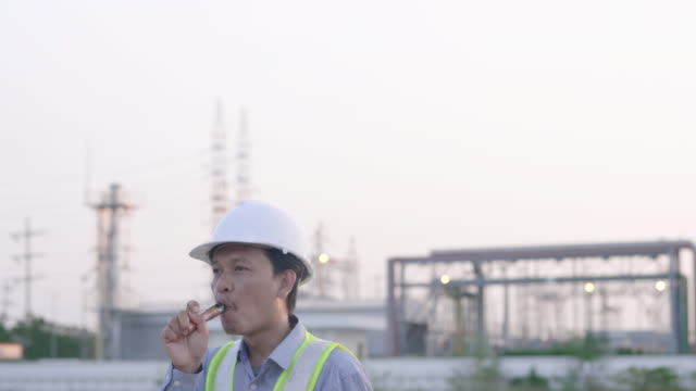 Engineers male smoking e-cigarette in front of power plant. Energy power station area. Relax from work concept Engineers male smoking e-cigarette in front of power plant. Energy power station area. Relax from work concept generation x stock videos & royalty-free footage