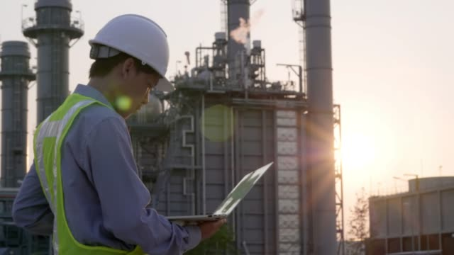 Engineers male working with laptop and operate the radio for workers security control at power plant. Energy power station area with sky, sunset. Concept safety,industry
