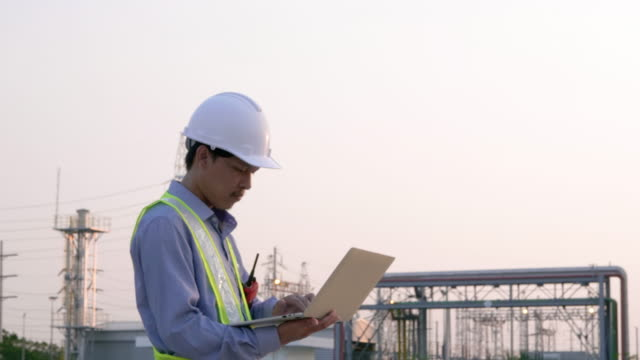 engineers male working with laptop and operate the radio for workers security control at power plant. energy power station area with sky, sunset. concept safety,industry - sottostazione elettrica video stock e b–roll
