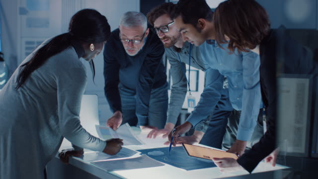 engineers meeting in technology research laboratory: engineers, scientists and developers gathered around illuminated conference table, talking and finding solution, inspecting and analysing industrial engine design. - progettare video stock e b–roll