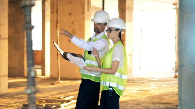 Engineers walking in unfinished building with a laptop, side view. Workers walking in a building, holding a laptop. occupational safety and health stock videos & royalty-free footage