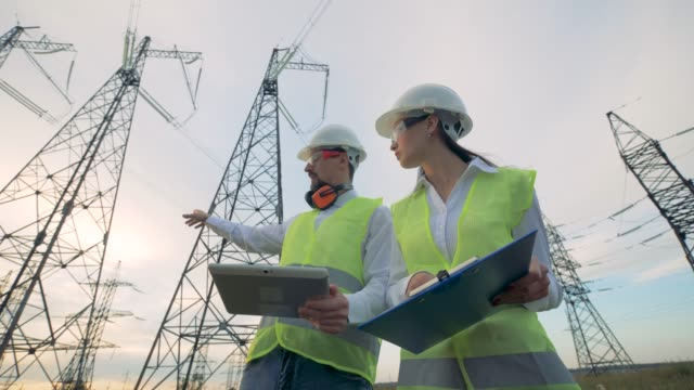 Engineers work with a tablet on power lines. Power lines, power substation, electrical substation, electric substation concept. video