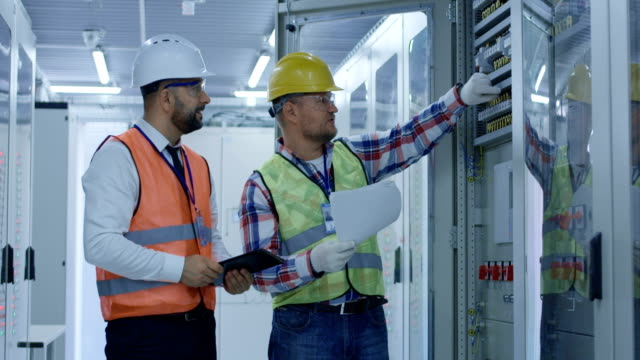 Engineers working with electrical equipment on station Adult men with tablet and papers working on solar plant in hall of control center having discussion occupational safety and health stock videos & royalty-free footage