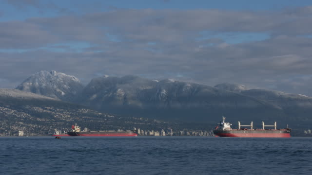 English Bay, Snowy Mountains, Vancouver Timelapse 4K Freighters anchored in front of the West Vancouver shoreline of English Bay. The Coast Mountains rise in the background. British Columbia, Canada. coastal feature stock videos & royalty-free footage