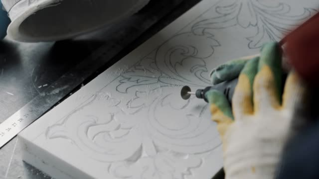 Engraver cut out the pattern in marble slab, the stencil is applied in advance Hand making one part of the marble fireplace, part of the marble fireplace craftsman architecture stock videos & royalty-free footage