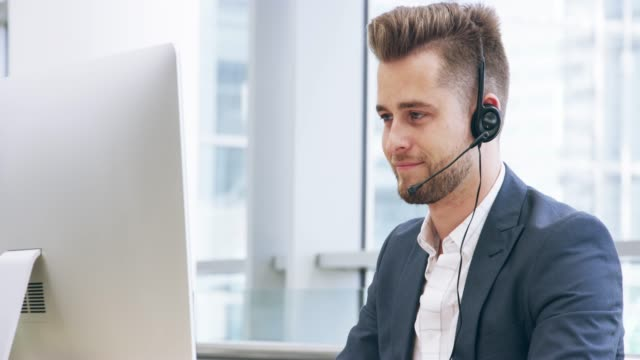 I enjoy solving customer issues 4k video footage of a young call centre agent working in an office call center stock videos & royalty-free footage