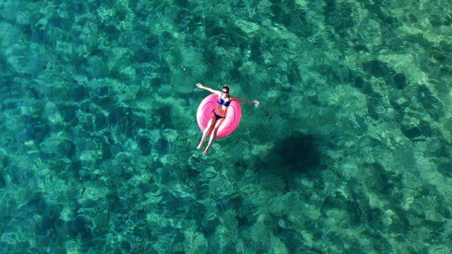 Enjoy vacations Enjoy vacations, young woman relaxing on the sea surface. floating on water stock videos & royalty-free footage