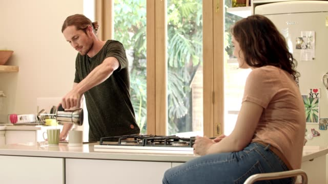 Enjoy your coffee my love 4k video footage of a young couple spending time together in their kitchen at home brown hair stock videos & royalty-free footage