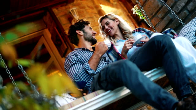 Enjoying a cup of tea at the porch. Closeup ow angle side view of a happy couple on a rustic porch swing at a vacation house. They are having some tea and casual conversation. porch stock videos & royalty-free footage