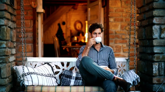 Enjoying a cup of tea at the porch. Closeup front view a pensive man drinking some tea and taking some time alone to rethink things in his life. porch stock videos & royalty-free footage