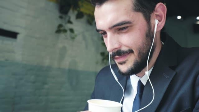 vidéos et rushes de bénéficiant d'un bon café tout en utilisant des écouteurs. - podcasting