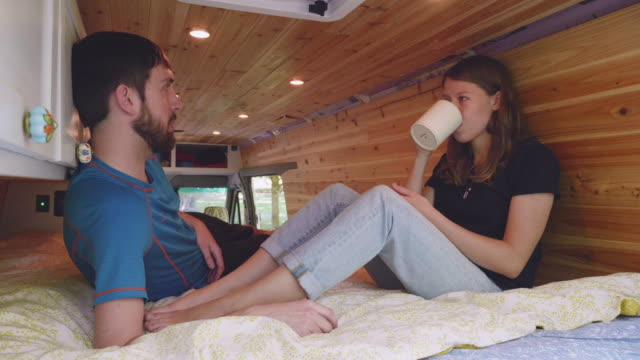 Enjoying a hot drink on the bed of their van Young couple sitting on the bed of their van while enjoying a hot drink rv interior stock videos & royalty-free footage