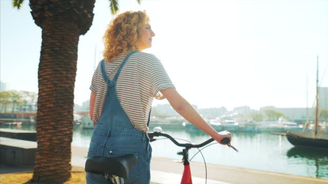 Enjoying a perfect weekend. Happy young woman relaxing outdoor in a beautiful sunny day. She is with her bicycle, admiring the view near the harbor in Barcelona. life balance stock videos & royalty-free footage