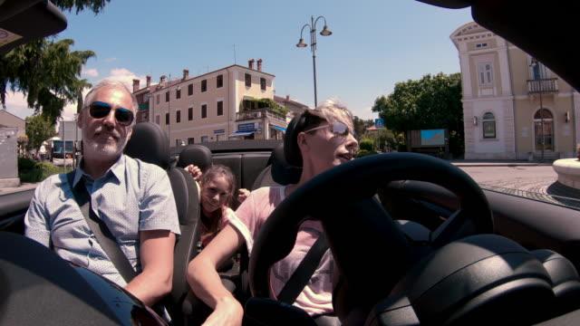 Enjoying a ride with a Convertible car around a Mediterranean small Town