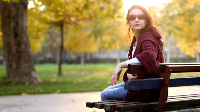 Enjoying autumn woman on park bench video