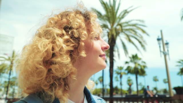 stockvideo's en b-roll-footage met genieten van het stadsleven in barcelona. - blond curly hair