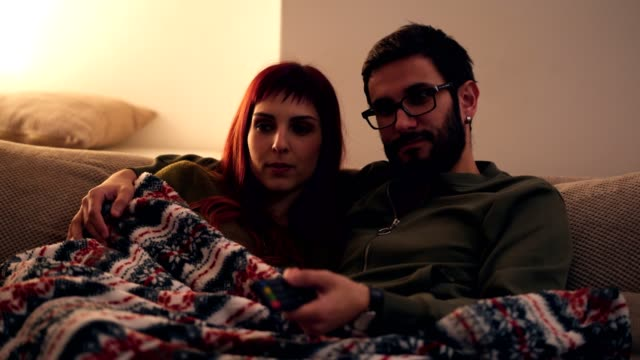 Enjoying good movie at night Smiling couple is sitting embraced in living room covered with blanket and watching TV. heterosexual couple stock videos & royalty-free footage