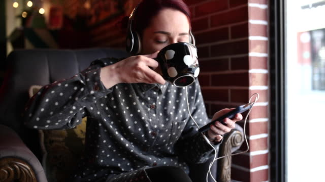 Enjoying in her playlist on phone and tea in cafe