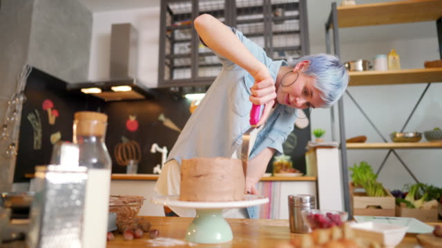 Enjoying making her favorite cake Young woman making a cake at her kitchen. blue hair stock videos & royalty-free footage