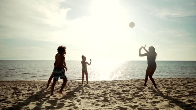 Enjoying summer vacation on the beach Smiling family is playing volleyball on the beach during sunny day. volleyball sport stock videos & royalty-free footage