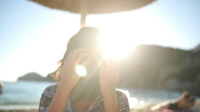 godersi il tramonto in spiaggia - spettinato video stock e b–roll