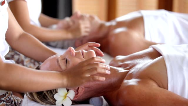 enjoying the blissful getaway they deserve - massage stok videoları ve detay görüntü çekimi