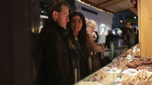 vídeos de stock e filmes b-roll de enjoying the christmas market together - passagem de ano
