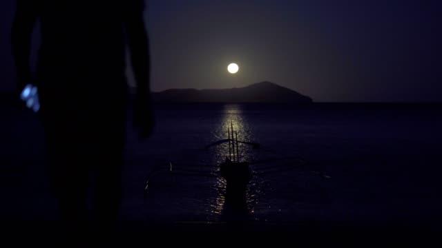 stockvideo's en b-roll-footage met genieten van het maanlicht op het strand - er even tussenuit