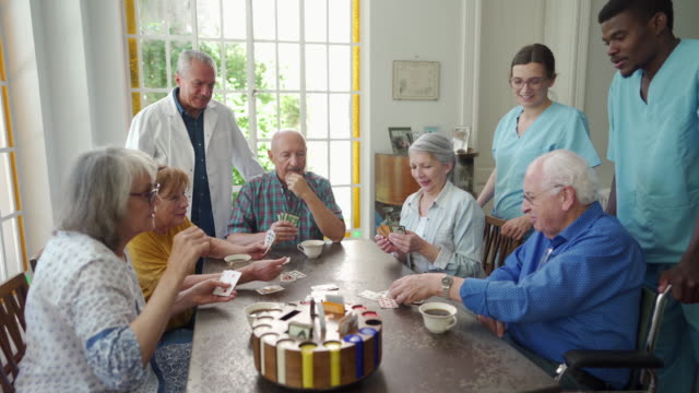 Enjoying their card game Group of Argentinian senior people playing cards and drinking tea while healthcare workers standing around them playing card stock videos & royalty-free footage