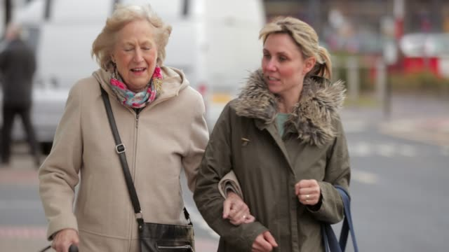 Enjoying Their Day Out Shopping A mature woman help a senior woman out of a car as she takes her to the shops sociology stock videos & royalty-free footage
