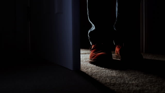 Entering a dark room, close up of man's feet. DS Low angle shot of a man's feet as he enters a dark room, stands for a while then closes the door. He is wearing casual tan shoes and denim jeans.  Dolly shot. anticipation stock videos & royalty-free footage