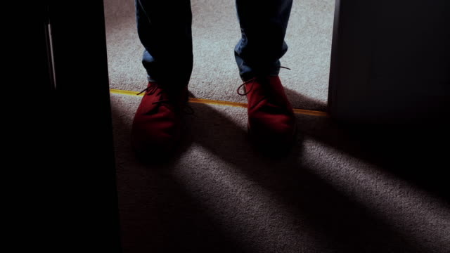 Entering a dark room, man's feet high angle view. DS High angle shot of a man's feet as he enters a dark room, stands for a while then closes the door. He is wearing casual tan shoes and denim jeans. Dolly shot. ominous stock videos & royalty-free footage