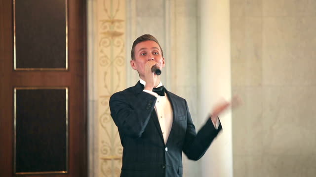 Entertainer leads event speaks into the microphone gesturing video