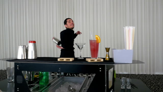 Entertainer making flair bartending moves with shaker at a bar in slow motion video