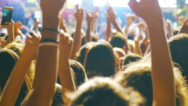 slow-mo: entusiastisk publik på en rockkonsert - åskådare människoroller bildbanksvideor och videomaterial från bakom kulisserna