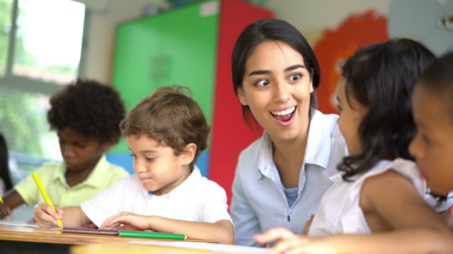 Enthusiastic teacher helping her students at class