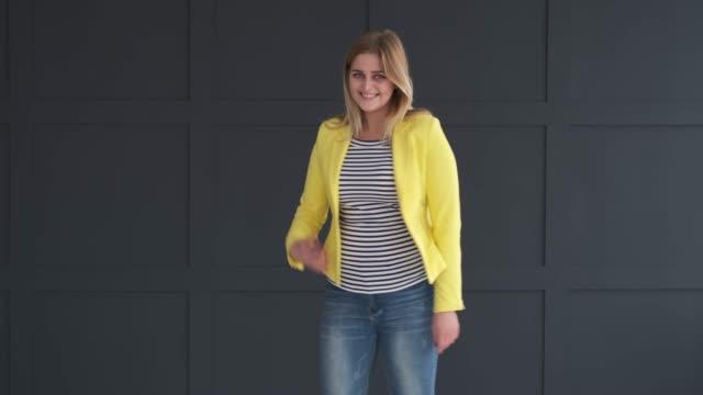 stockvideo's en b-roll-footage met enthousiaste vrouw poseren in gele blazer - men blazer