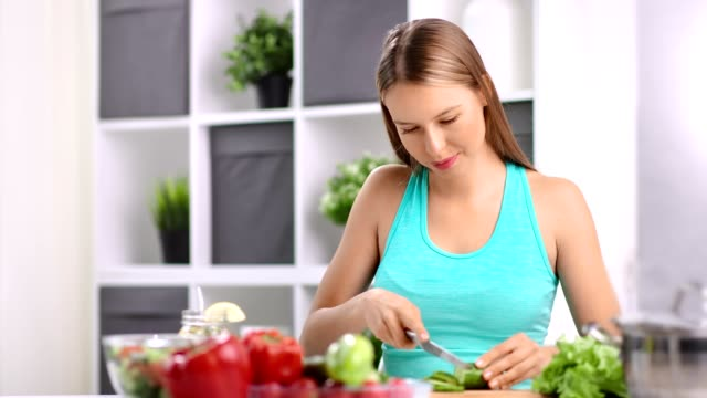 Enthusiastic young housewife chopping cucumber cooking vegetable salad in kitchen at home