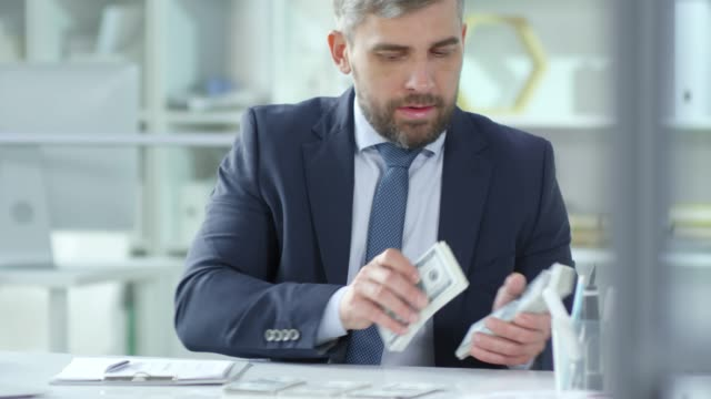 Entrepreneur Counting Stacks of Money at Office Desk video