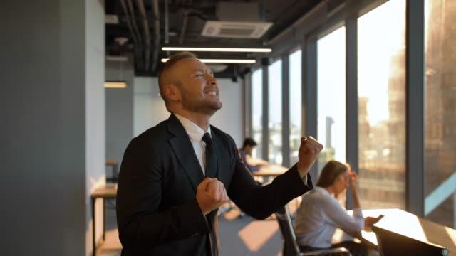 Danse d'entrepreneur par la fenêtre dans le bureau pendant le coucher du soleil - Vidéo