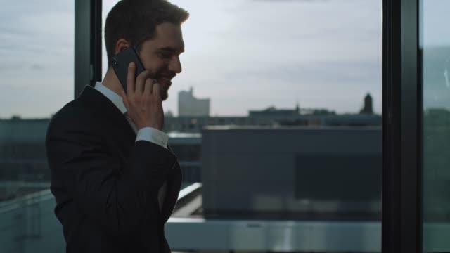 entrepreneur discussing on smartphone in office - dobrze ubrany filmów i materiałów b-roll
