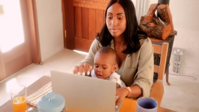 entreprenör mor med lilla son blogga på laptop hemma - working from home bildbanksvideor och videomaterial från bakom kulisserna