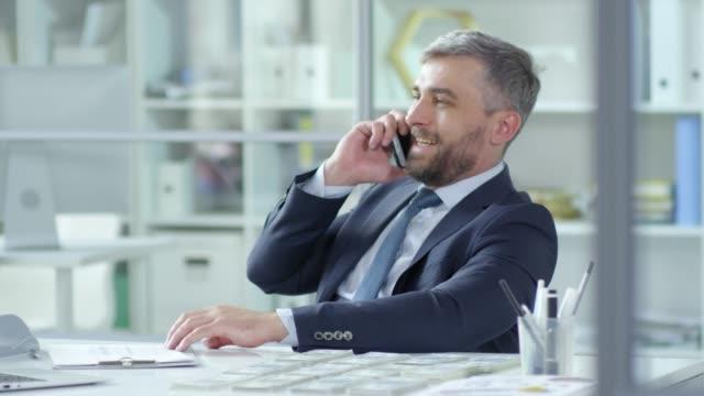 vídeos de stock e filmes b-roll de entrepreneur speaking on phone at desk with money stacks - corruption