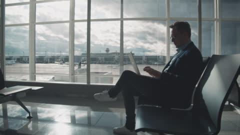 imprenditore che usa laptop in attesa in aeroporto - aeroporto video stock e b–roll