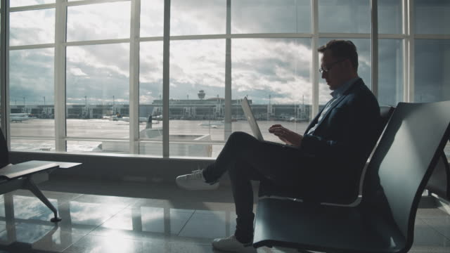 stockvideo's en b-roll-footage met ondernemer met behulp van laptop tijdens het wachten op luchthaven - vliegveld vertrekhal