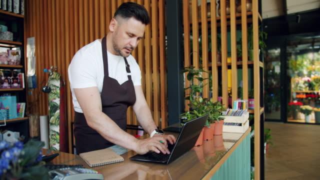 çiçekçi dükkanında dizüstü bilgisayarla çalışan girişimci not defterine yazıp yazıyor - küçük stok videoları ve detay görüntü çekimi